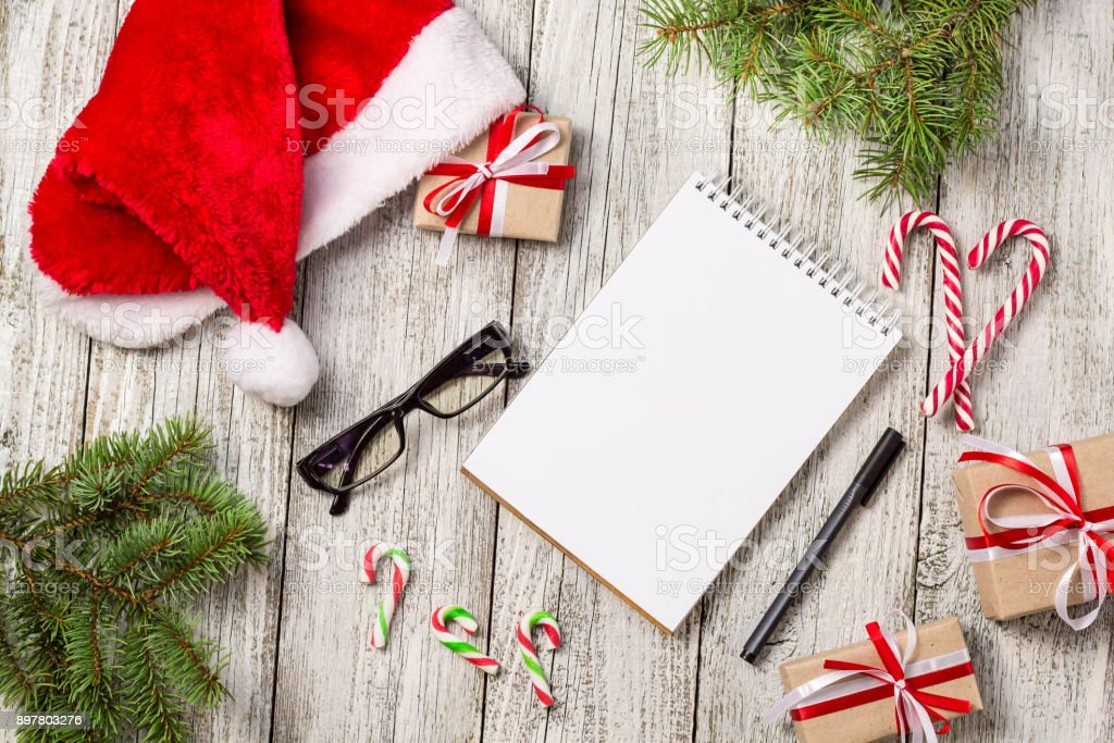 Christmas and Business Items with Copy Space cropped Santa Cap Notepad Pen Glasses and decorated Gift Box and fir tree stock photo