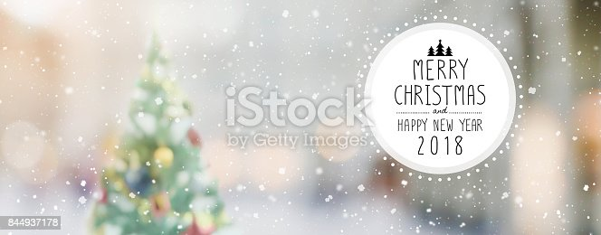 istock Christmas and Happy new year 2018 on blurred bokeh christmas tree with snowfall banner background 844937178