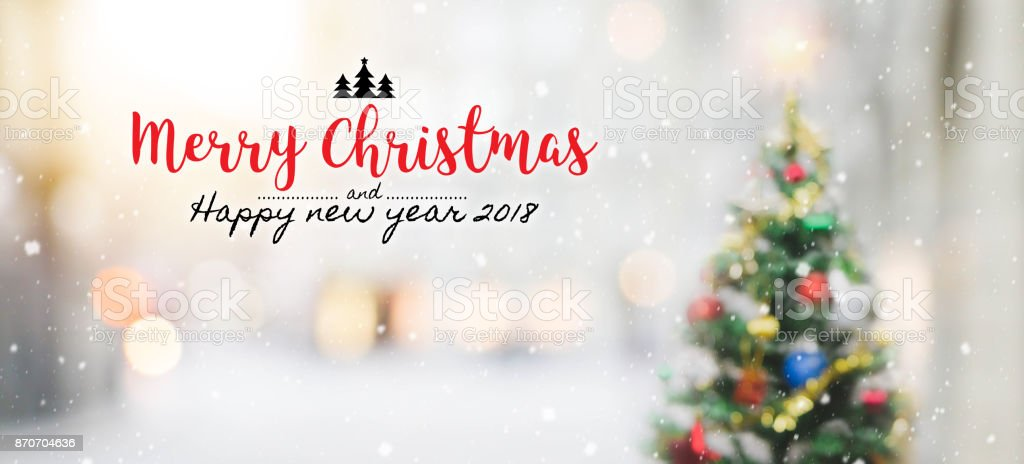 Christmas and Happy new year 2018 on blurred bokeh christmas tree with snowfall background. stock photo