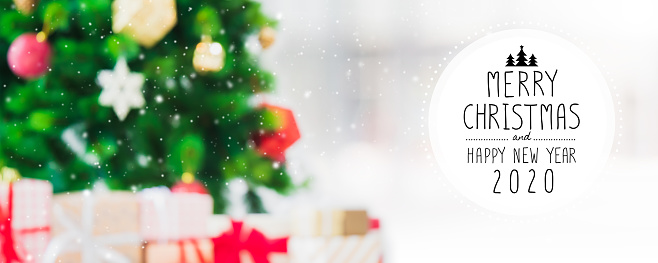 istock Christmas and Happy new year 2020 on blurred bokeh christmas tree with snowfall banner background. 1185418024