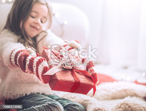 579124316 istock photo Christmas and Holiday concept little girl with a gift 1066323560