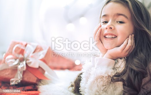 579124316 istock photo Christmas and Holiday concept little girl with a gift 1066323594