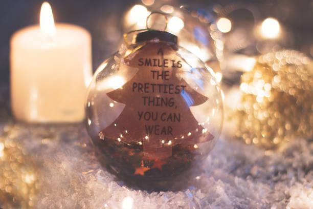 """weihnachten und neujahr hintergrund - glaskugel mit zitat """"ein lächeln ist die schönste sache, die sie tragen können"""", kerze und weihnachten lichter auf holztisch - zitate weihnachten stock-fotos und bilder"""