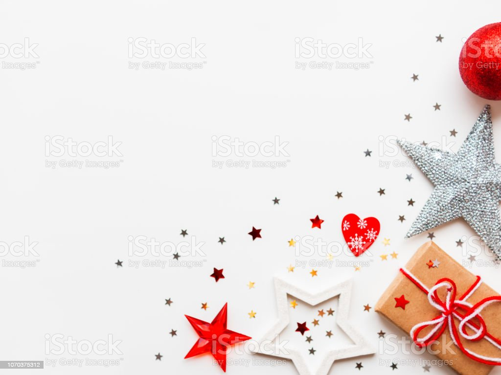 Christmas and New Year background with decorations and present wrapped in craft paper with stars and red heart. Flat lay, top view. Place for text. stock photo