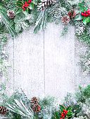 Christmas and New Year background with fir branches, holly and snowfall on wooden white board