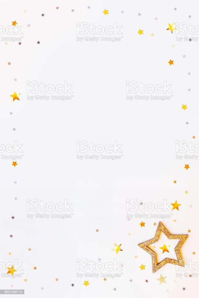 Christmas and New Year background with sparkling golden stars frame and confetti. Holiday symbols on white background with place for text. stock photo