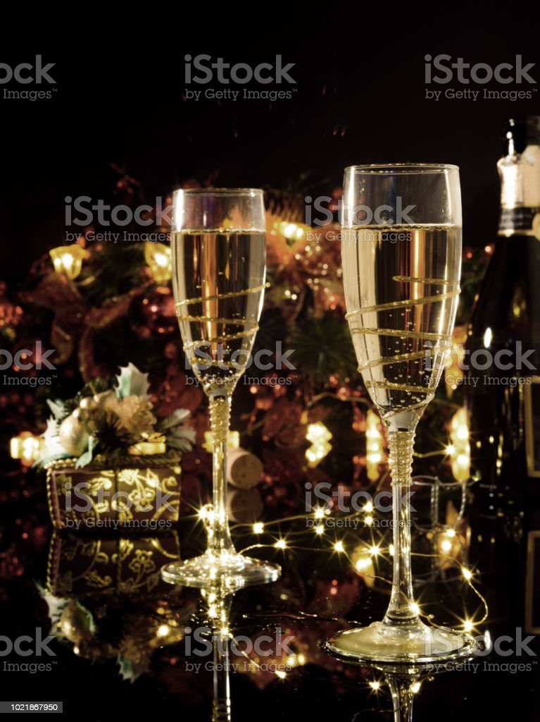 Christmas and New Year celebration with champagne. New Year holiday decorated table. Two Champagne Glasses, vintage toned. stock photo