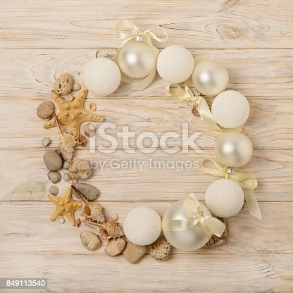 istock Christmas and New Year. Christmas wreath of Christmas-tree white toys in marine style, shells, stones and starfish. 849113540