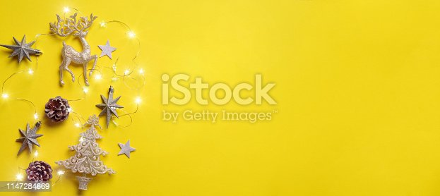 istock Christmas and new year concept. Greeting banner with copyspace. Shiny silver deer, stars, fir-tree, garland, bokeh on yellow background. Top view, flat lay 1147284669