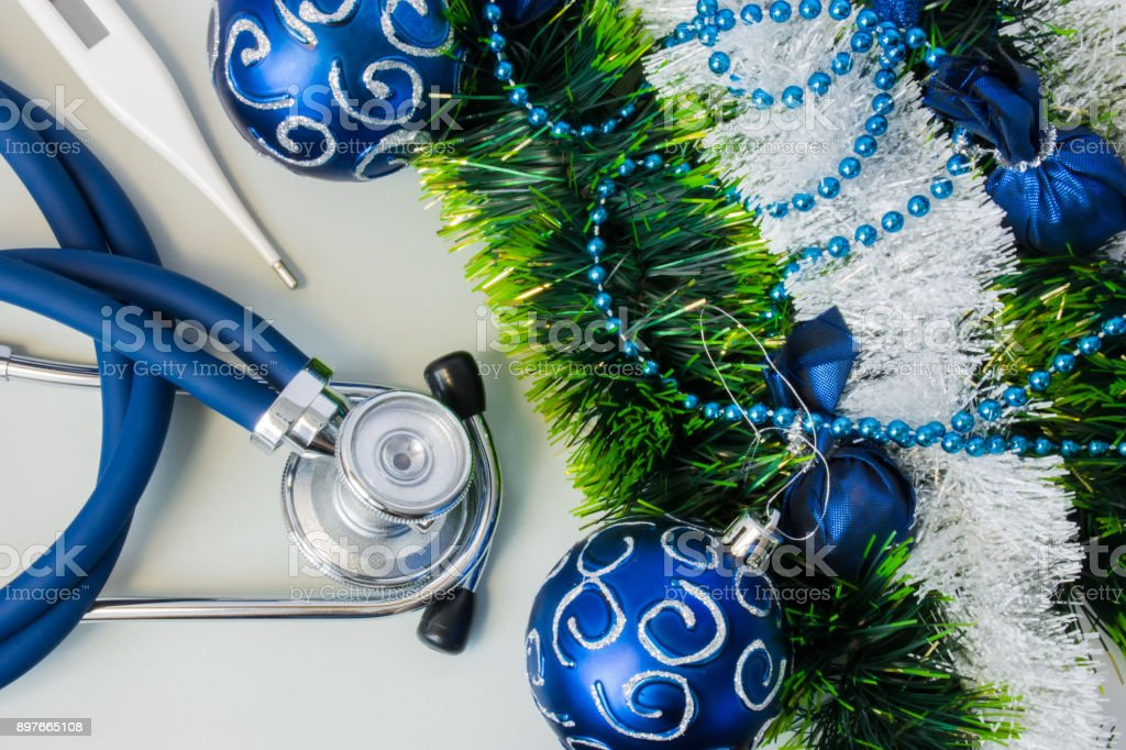 Christmas and New Year decorations near medical equipment. Medical stethoscope and thermometer lying near artificial snow with glitter, toys and blue balls on Christmas tree. New Year in Medicine stock photo