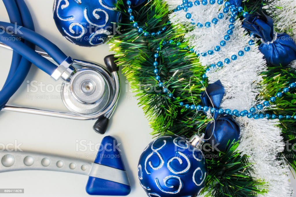Christmas and New Year decorations near medical equipment. Neurology hummer and medical stethoscope lying near artificial snow with glitter, toys and blue balls on Christmas tree. New Year in Medicine stock photo