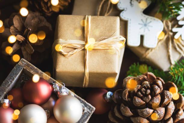 Weihnachten und Neujahr Geschenk-Boxen in braunen Papier Kiefer Kegel Baum Dekorationen Kugeln in Holz-Box in goldenen funkelnden Lichtern gewickelt – Foto