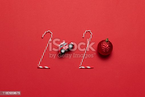 istock Christmas and New Year holiday 2020 inscription from various decorated objects classic red glass baubles ball, toy car on a red background. 1182659675