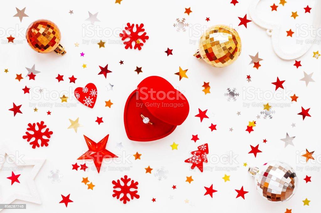 Weihnachten und Neujahr Urlaub Hintergrund mit Dekorationen und Verlobungsring mit Diamant im Herz Geschenkkarton. Glänzende Kugeln, Filz Schneeflocken und Sterne Konfetti. Flach legen, Top Aussicht. – Foto