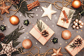 Christmas and New Year holiday decorations in green and golden colors on gray concrete backdrop. Craft handmade gift boxes, golden balls, stars and cones.  Flat lay style.