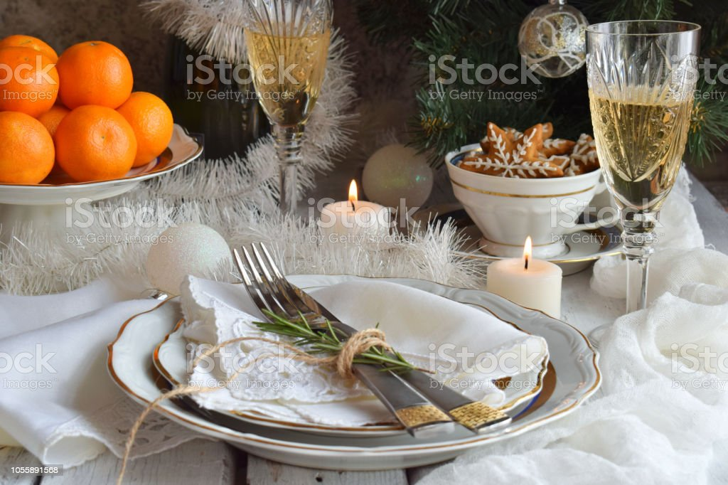 Christmas And New Year Holiday Table Setting. Celebration. Place setting for Xmas Dinner. Holiday Decorations. Decor. Plate, Tangerines, Glasses With Champagne, Fruit cake stock photo