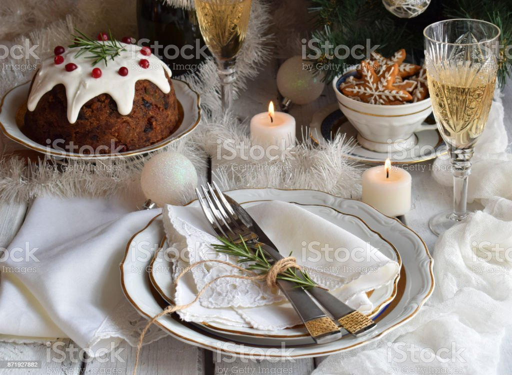 Christmas And New Year Holiday Table Setting. Celebration. Place setting for Xmas Dinner. Holiday Decorations. Decor. Plate, Tangerines, Glasses With Champagne, Fruit cake. stock photo