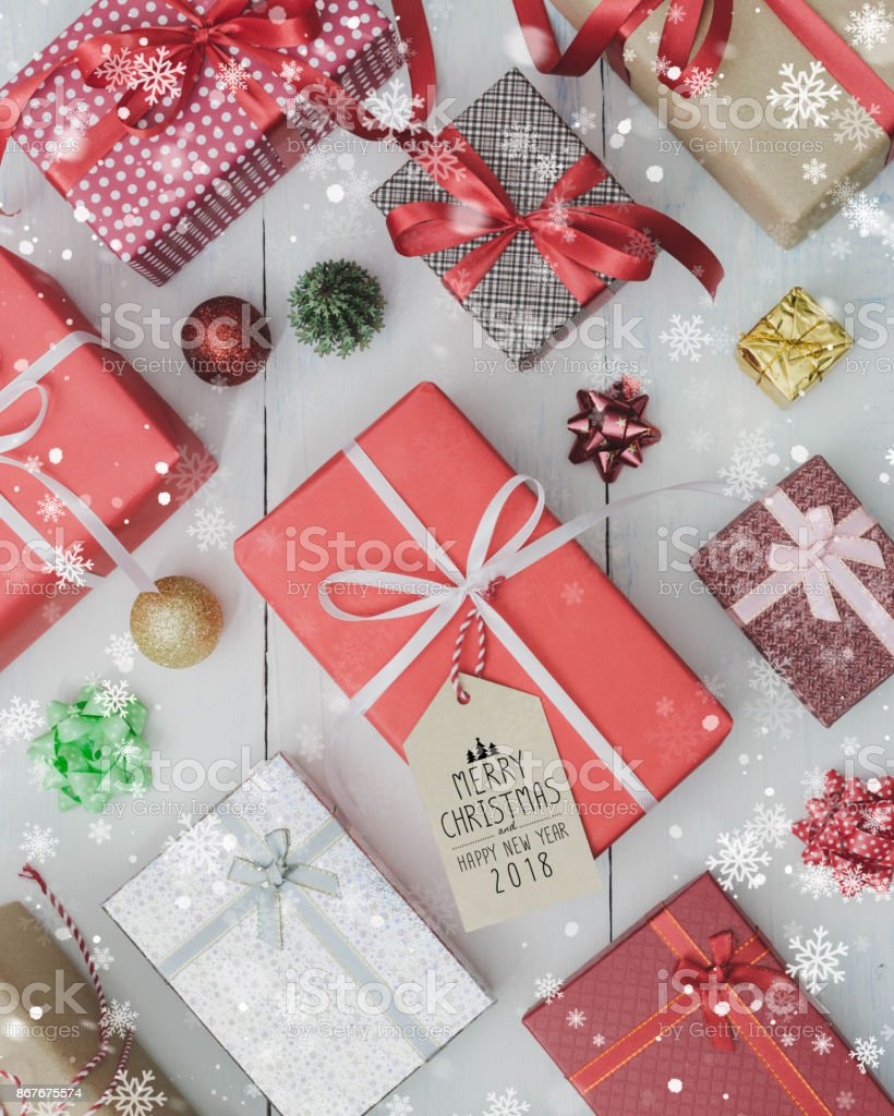 Christmas and New Year holidays gift box on white wooden table with falling snow effect.Flat lay with Merry Christmas & Happy New Year 2018 sign.Gifts and congratulations concept.'n stock photo