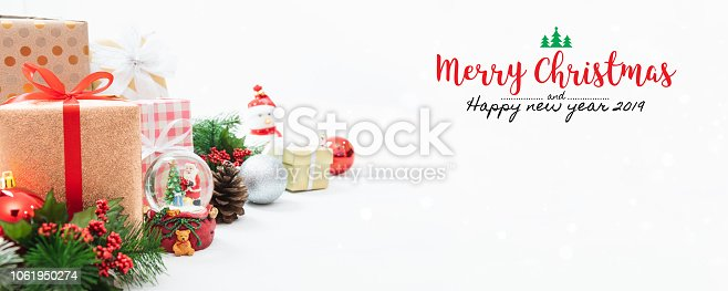 istock Christmas and New Year holidays gift box with decorative ornament on table with falling snow effect banner.Merry Christmas & Happy New Year 2019.Gifts and congratulations concept. 1061950274