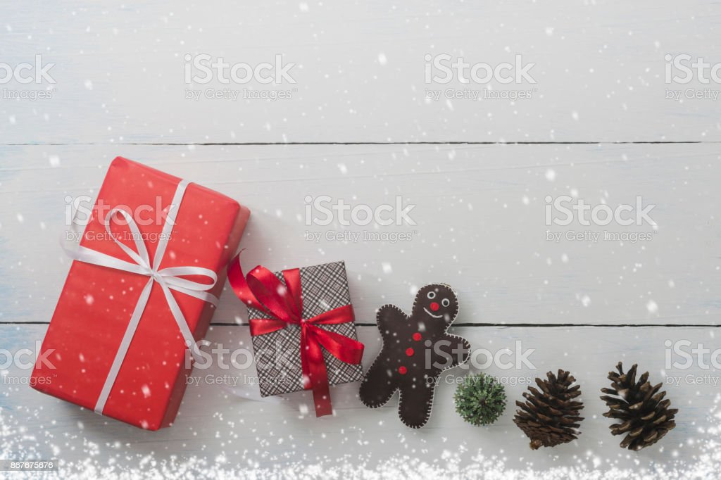 Christmas and New Year holidays gift box with decorative ornament on white wooden table with falling snow effect.Flat lay with copy space background.Gifts and congratulations concept. stock photo