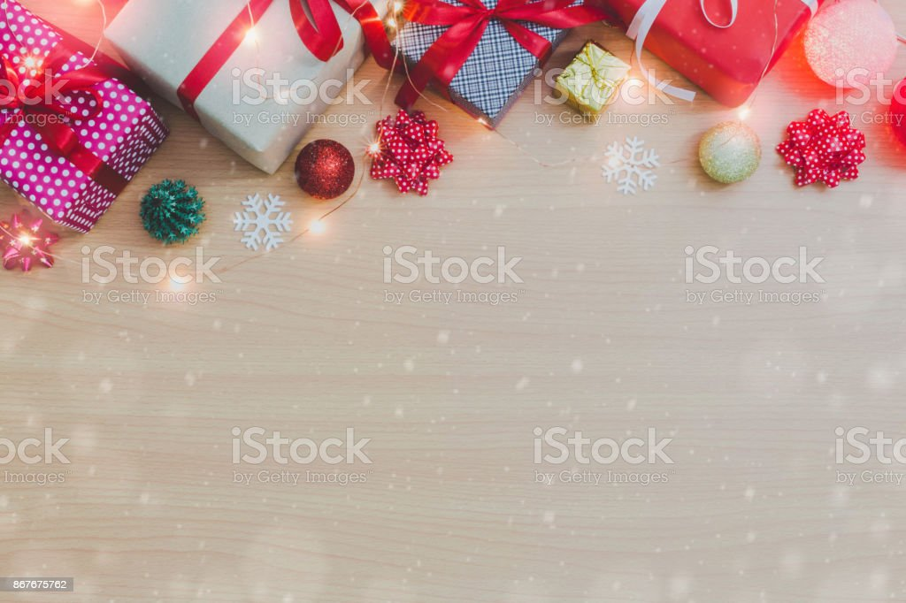 Christmas and New Year holidays gift box with decorative ornament on wooden table and copy space.Gifts and congratulations concept.Falling snow effect background. stock photo