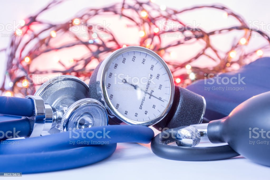 Christmas and New Year in internal medicine, general practice. Medical stethoscope and blood pressure gauge (sphygmomanometer) in foreground with blurred lights bulbs Christmas garlands in background stock photo