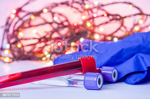 istock Christmas and New Year in medical and science laboratory. Laboratory assistant equipment - test tubes with blood and gloves in foreground with blurred lights bulbs Christmas garlands in background 897077314