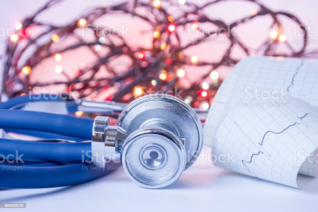 Christmas and New Year in medicine, general practice or cardiology. Medical stethoscope and ECG tape with pulse trace in foreground with blurred lights bulbs Christmas garlands in background. stock photo