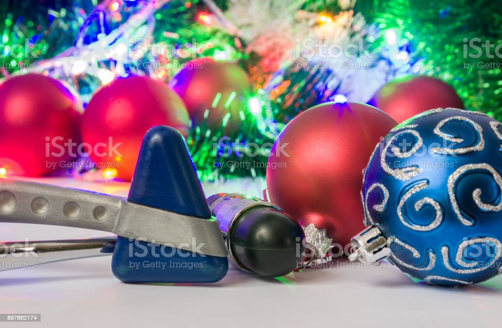 Christmas and New Year in neurology, medicine or neuroscience photo - two neurological hammer are located near balls for Christmas tree in blurry background with electric garlands lights and toys stock photo