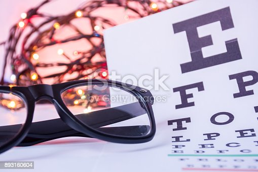 istock Christmas and New Year in ophthalmology optometry. Eyeglasses and ophthalmological table for visual acuity test in foreground with blurred lights bulbs Christmas garlands in background 893160604