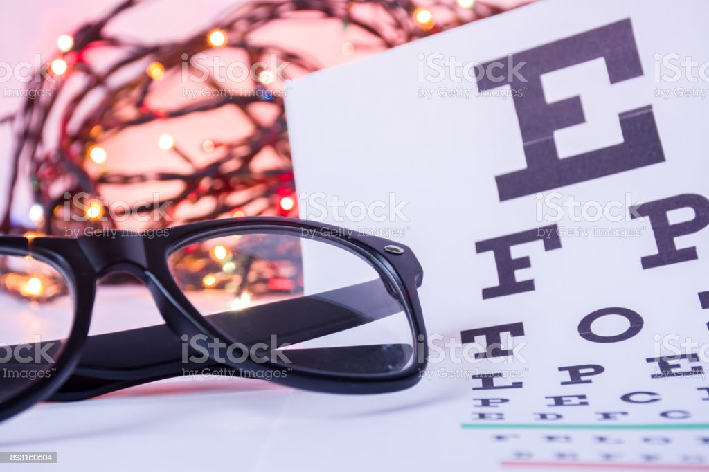 Christmas and New Year in ophthalmology optometry. Eyeglasses and ophthalmological table for visual acuity test in foreground with blurred lights bulbs Christmas garlands in background stock photo