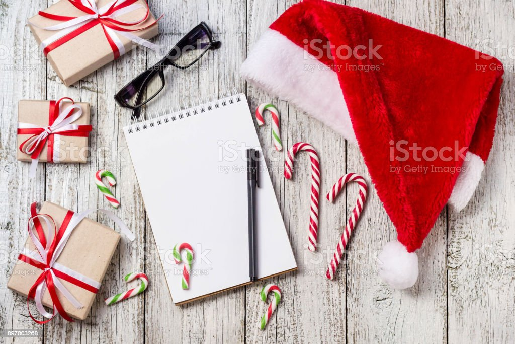 Christmas and New Year Items with Copy Space Santa Cap Notepad Pen Glasses and decorated Gift Boxes stock photo
