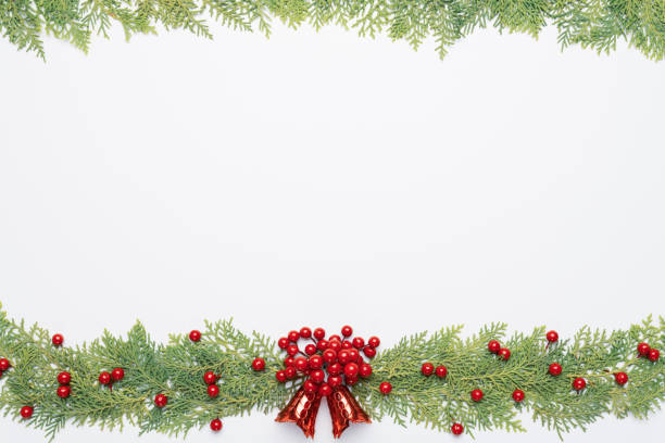 christmas and new year's composition. top view of spruce branches, pine cones, red berries and bell on white background. - floral garland stock pictures, royalty-free photos & images