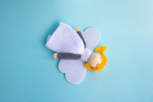 Christmas angel doll made of fabric and wood on a blue background.