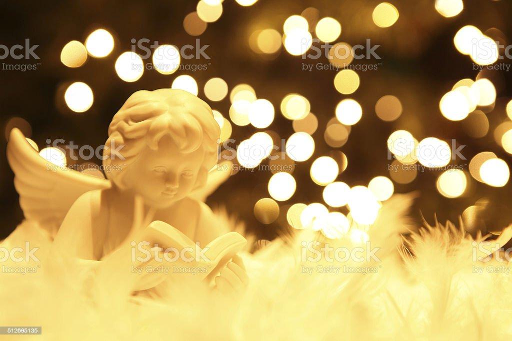 christmas angel figurine and blur christmas lights royalty free stock photo