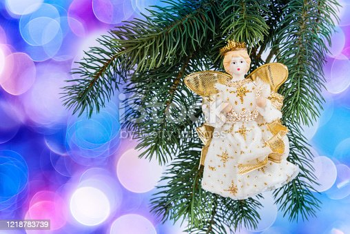 Christmas angel hanging on a spruce twig.