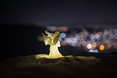 istock christmas angel on blur bokeh city lights at night on background. Little white guardian angel in snow. 1076299912