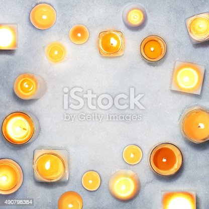 Composition with white candles in the snow seen from above for an arty, abstract look. Copy space in the middle.