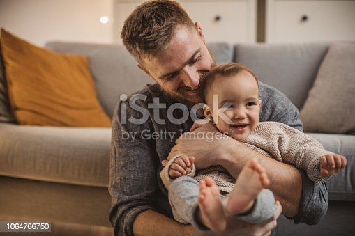 Father playing on bed with his young son, it's Christmas and they enjoy in time together. Father carrying son