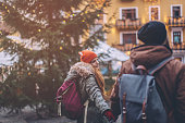 Young couple at winter mountain village. Walking and enjoying in nature. Wearing warm clothes, backpack and enjoying. Winter day. Christmas tree is decorated with festive string lights. Hallstatt lake, Austria.