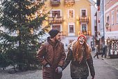 Young couple at winter mountain village. Walking and enjoying in nature. Wearing warm clothes, backpack and enjoying. Winter day. Christmas tree is decorated with festive string lights.