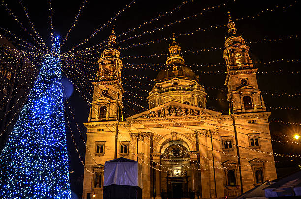 Christmas at St. Stephens Cathedral at Night - Budapest The iconic St. Stephens Basilica at Night with a Christmas Tree. basilica stock pictures, royalty-free photos & images