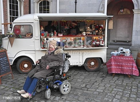 30th December 2019 Dublin, Ireland. Woman in a motorised wheelchair in front of a hot drinks and snacks vintage van at the 'Christmas at the Castle' outdoor Christmas market at Dublin Castle, Dame St