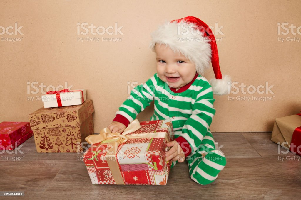 Christmas Baby In Santa Hat Holding Present Gift Box Stock Photo