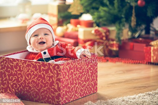Cute little baby boy in Santa hat sitting inside of the red gift box next to the Christmas tree.