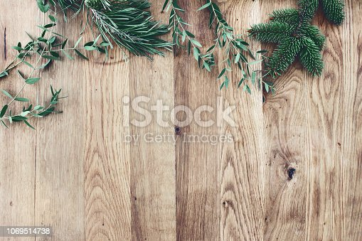 istock Christmas background. Border, frame of green fir, eucalyptus and pine tree branches on old wooden oak table. Winter festive banner. Vintage look. Flat lay, top view. 1069514738