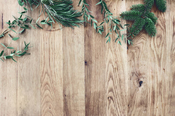 christmas background. border, frame of green fir, eucalyptus and pine tree branches on old wooden oak table. winter festive banner. vintage look. flat lay, top view. - christmas table foto e immagini stock