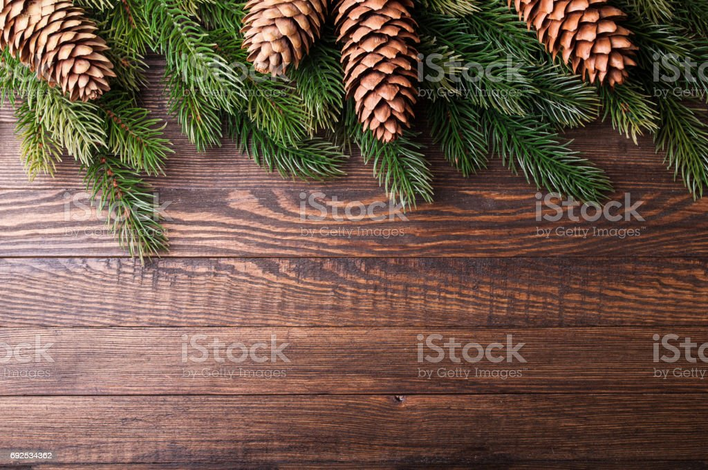 Christmas background. Christmas tree with decoration and pinecone on old wooden background. Xmas card. Top view. Copy space stock photo