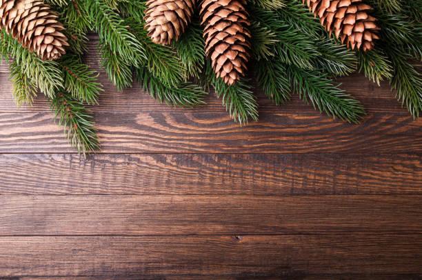Fondo de Navidad. Árbol de Navidad con decoración y piña en el fondo de madera vieja. Tarjeta de Navidad. Vista superior. Copia espacio - foto de stock