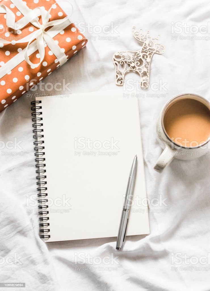 Christmas background. Clean blank notepad, coffee, gift box, christmas decorations on light background, top view. Flat lay, cope space stock photo